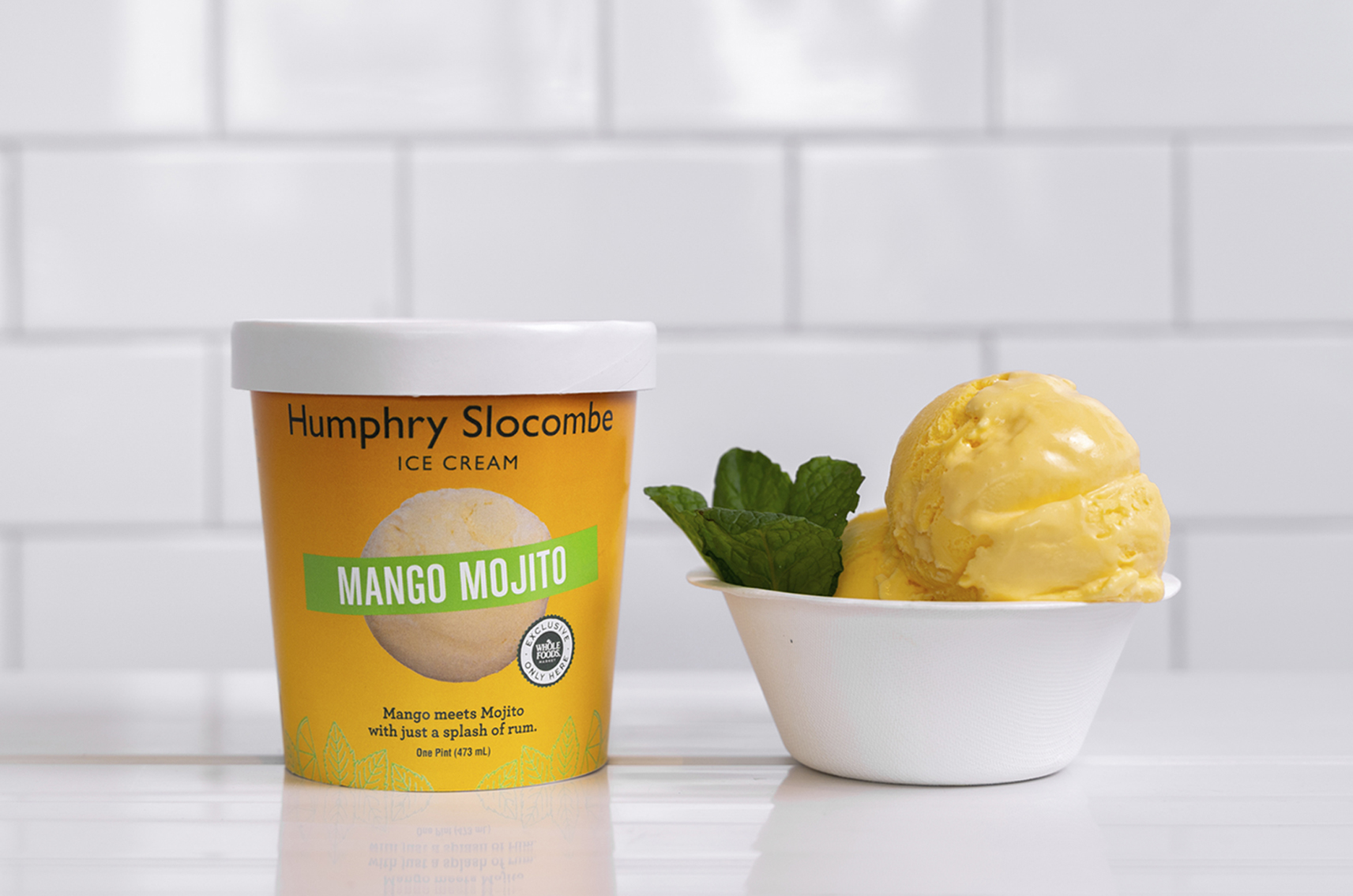 Mango Mojito icecream pint and scoop in bowl with mint garnish