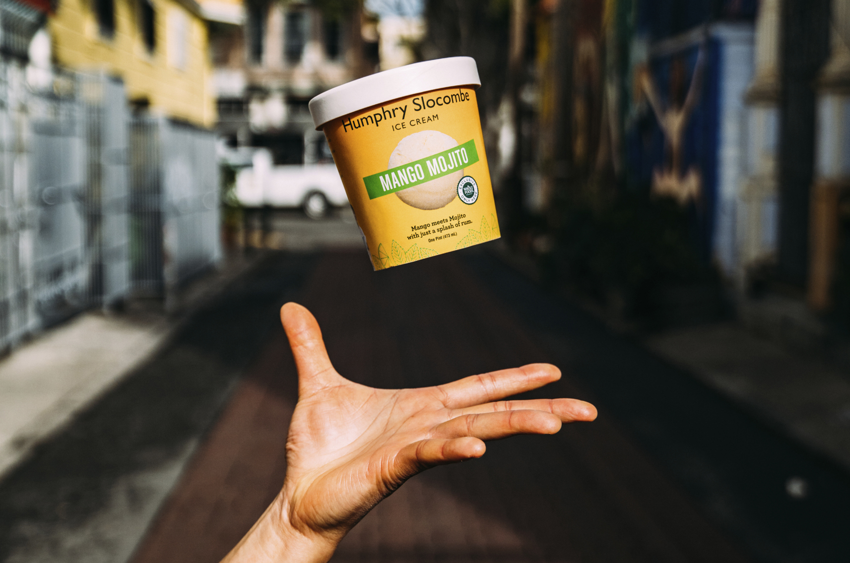 hand playfully tossing Mango Mojito pint into air