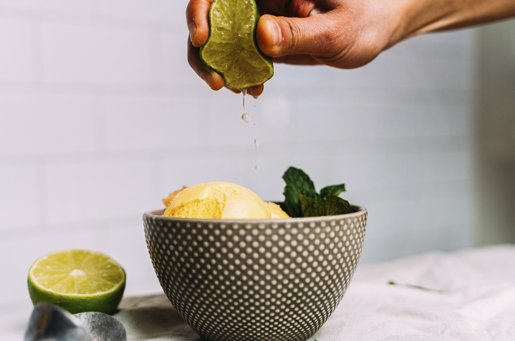 Person squeezing lime over bowl of mango mojito ice cream